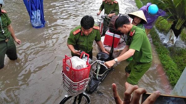 Đường ngập như sông, công an xắn quần lội nước giúp dân vượt qua