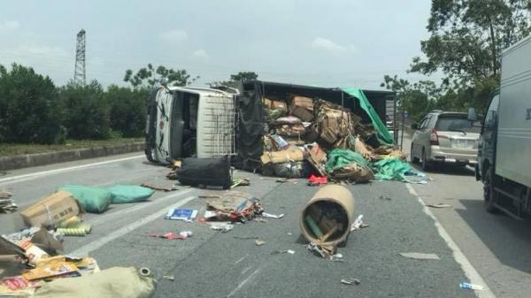 Bắc Ninh: Xe tải mất lái lật nghiêng, bìa cát tông tràn kín mặt đường QL18