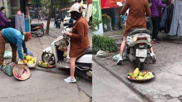 Phẫn nộ hình ảnh người phụ nữ mang bầu lái xe máy lên thẳng qua nia trái cây của cô bán hàng rong ven đường vì ngồi chắn trước cửa hàng