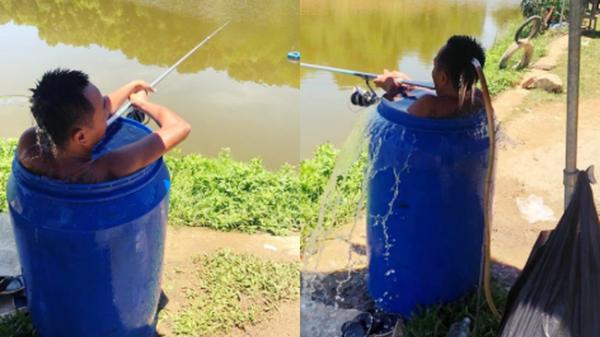 Người đàn ông ngồi hẳn trong thùng phuy vừa ngâm mình tránh nóng 40 độ, vừa thư giãn câu cá