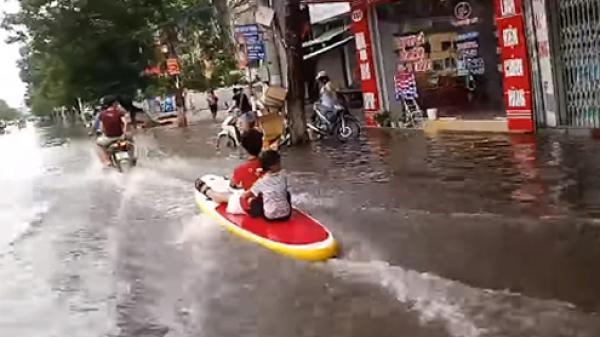 Trẻ em ngồi thuyền lướt sóng trên đường phố Hải Phòng
