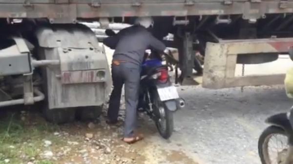 Xe đầu kéo mắc kẹt ngang đường hẹp, người dân phải dắt xe máy chui qua gầm để tiếp tục di chuyển