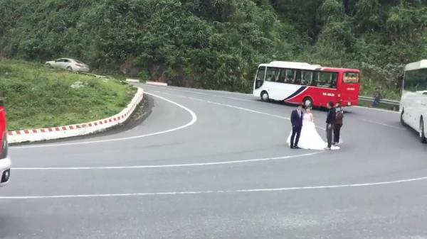 Cô dâu chú rể đứng đúng góc cua trên đèo Hải Vân tạo dáng chụp hình
