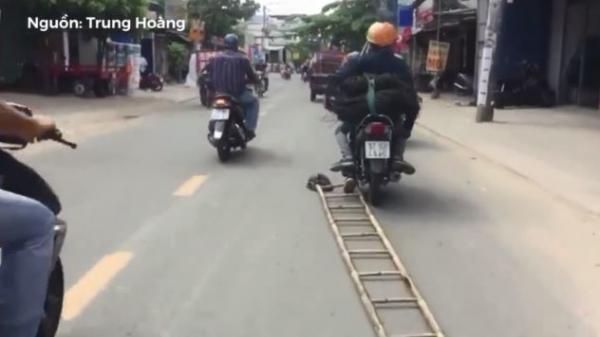 Hai thợ điện kéo lê thang đứng trên mặt đường, người dân đi đường ai cũng hãi