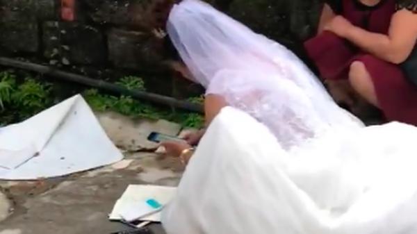 """Clip: Mặc kệ quan viên hai họ ăn cỗ, cô dâu vẫn miệt mài ngồi ngoài đường bấm máy tính """"cộng sổ"""""""