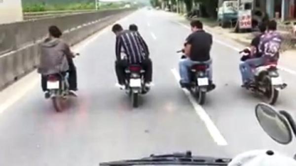 8 thanh niên đầu trần, dàn hàng ngang trước đầu ôtô trên quốc lộ
