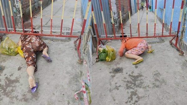 Bức xúc hình ảnh người dân trèo barie, 'bò ra đất' thông chốt kiểm soát để ra ngoài đi chợ