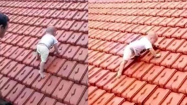 Xót xa hình ảnh em bé run rẩy bò lên nóc nhà để tránh dòng nước lũ đang dâng cao: Đôi tay bé nhỏ bám níu từng viên gạch