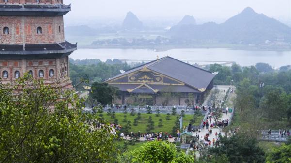 Dùng gậy xoa tiền vào tượng Phật để cầu may tại chùa Bái Đính