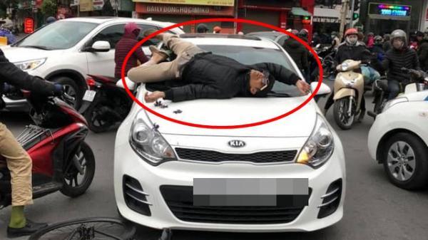 V.a ch.ạm giao thông không hòa giải được, chủ xe đạp leo lên nắp capo ô tô nằm