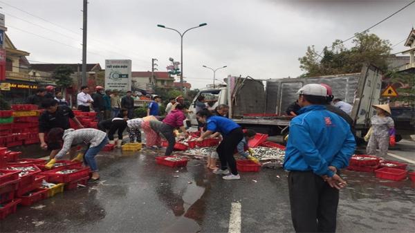 Xe tải lật nghiêng, dân xắn tay gom cá giúp tài xế