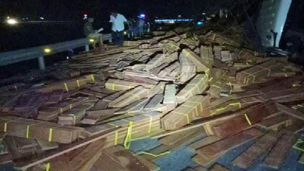 Xe đầu kéo bị lật, hàng chục tấn gỗ tràn xuống quốc lộ