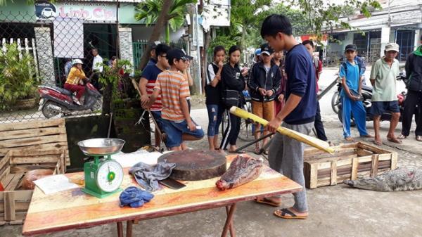 Dân hiếu kỳ vây quanh xem người đàn ông xẻ thịt cá sấu bán ngay bên đường