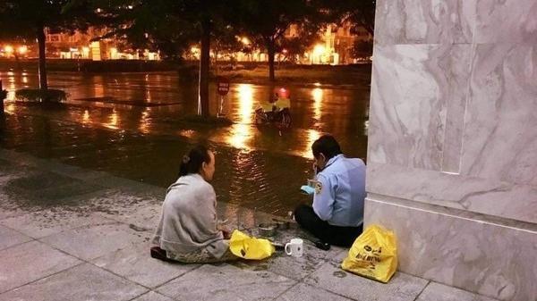 """Bức ảnh vợ đội mưa đưa cơm cho chồng làm bảo vệ khiến CĐM tan chảy: """"Có tiền cũng không mua được"""""""