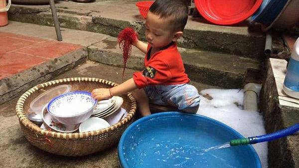 """Thấy bố mẹ ăn xong không dọn, bé trai vừa rửa bát vừa nói câu khiến cả nhà """"đứng hình"""""""