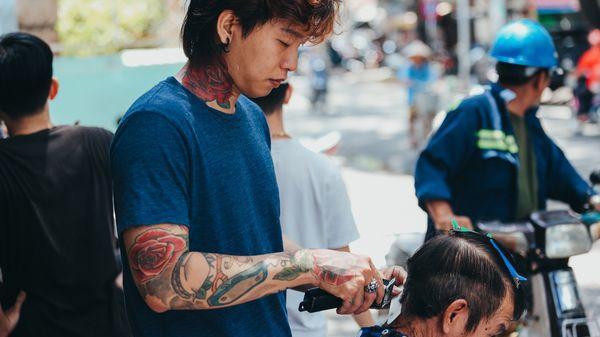 Ấm lòng chàng trai xăm trổ mở tiệm cắt tóc 0 đồng cho người nghèo Sài Gòn