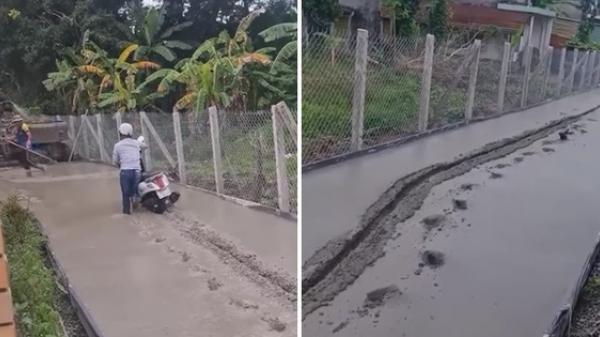 Người đàn ông cố dắt xe đi hết đường bê tông mới đổ, bao ánh mắt nhìn theo bất lực