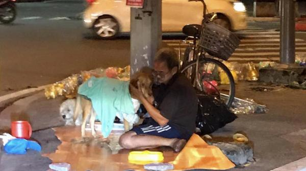 """Hình ảnh """"cay mắt"""" ở góc phố Sài Gòn: Cụ ông vô gia cư nhường áo, bón từng thìa thức ăn cho 2 con chó bị bỏ rơi"""