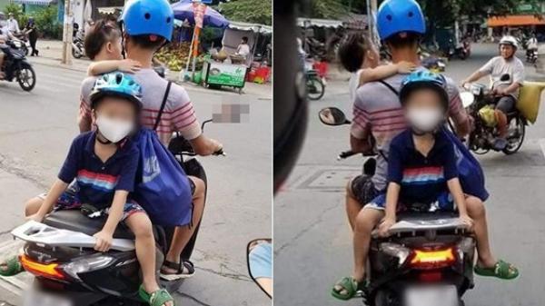 Hình ảnh thót tim trên đường phố Sài Gòn: Ông bố một tay bế con một tay lái xe máy, phía sau còn cho con trai ngồi đối lưng vắt vẻo