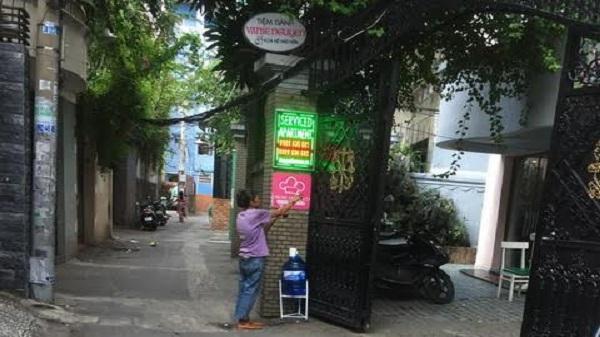 Người đàn bà đeo đầy trang sức đứng trước ngôi nhà sang trọng ở Sài Gòn