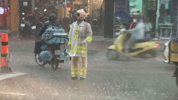 Hai nữ CSGT đội mưa điều tiết giao thông giữa Sài Gòn