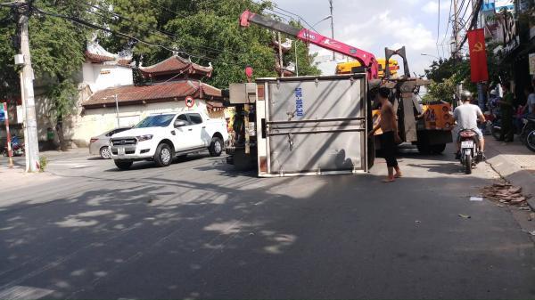 Xe tải lật nhào trên đường phố Sài Gòn, nhiều người đi đường thoát chết