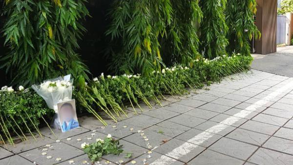 Người dân lặng lẽ đặt bông cúc trắng trước cổng trường để tưởng nhớ bé trai tử vong thương tâm trên xe đưa đón