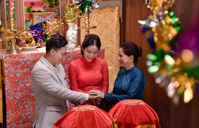 Diện chiếc áo dài cưới giản dị màu đỏ, được may theo lối cắt xẻ tà của trang phục áo dài xưa, Nam Em xuất hiện đầy rạng rỡ và hiền dịu trong ngày vui của mình.