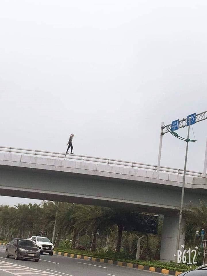Hình ảnh cô gái đi trên thành cầu trước khi nhảy xuống đất.