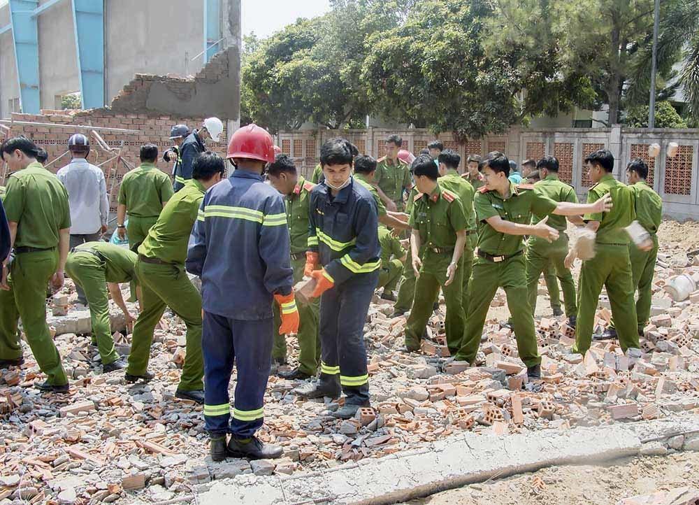 Lực lượng chức năng đào bới đống đổ nát để tìm kiếm, đưa các nạn nhân ra ngoài. Ảnh: Công an