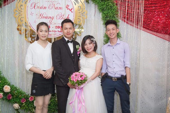 Kiên chụp ảnh cùng anh chị trong ngày cưới.