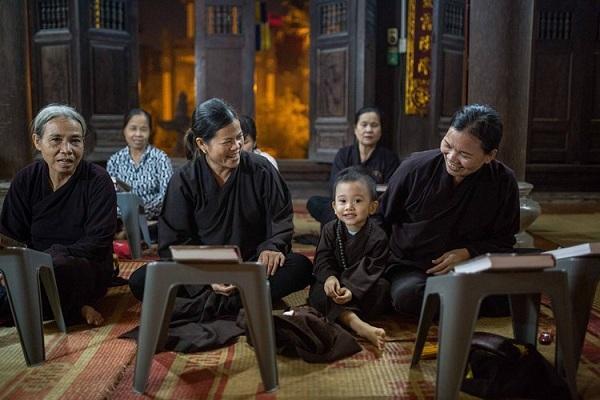Em bé đi tụng kinh trên chùa cùng bà ở Hà Nội. Ảnh: Mathieu Arnaudet - 500px.com.