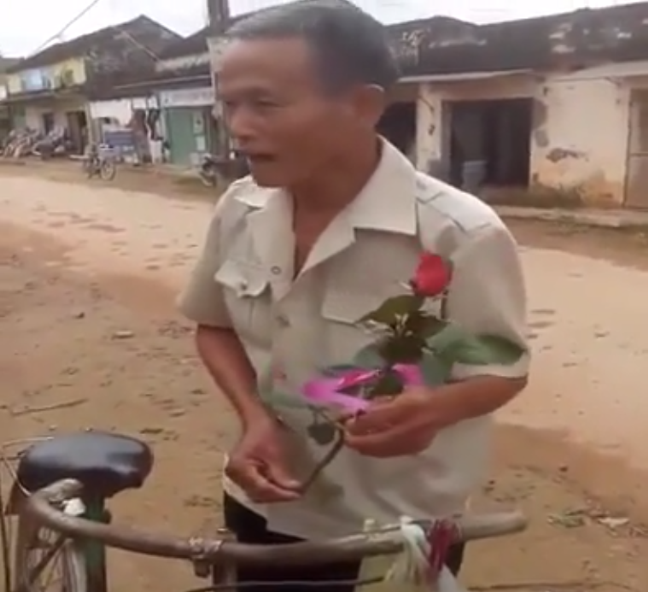 Cụ ông vui vẻ mua hoa tặng vợ ngày 20/10. Ảnh cắt từ clip.