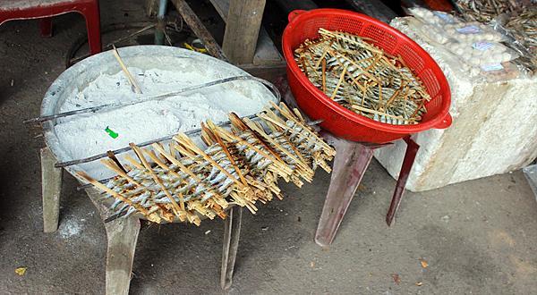 Các xiên được xếp cạnh bếp than ủ lửa âm ỉ, khi có khách, chủ quán sẽ nướng cá cho nóng. Ảnh. Đỗ Thảo