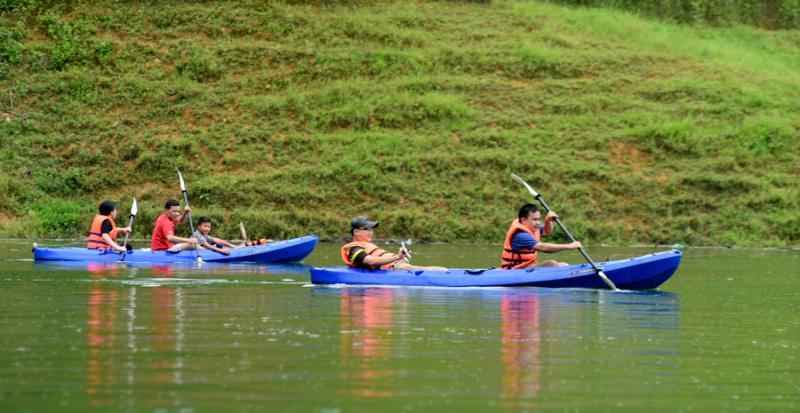 Khách du lịch bơi thuyền Kayak trải nghiệm trên lòng hồ.