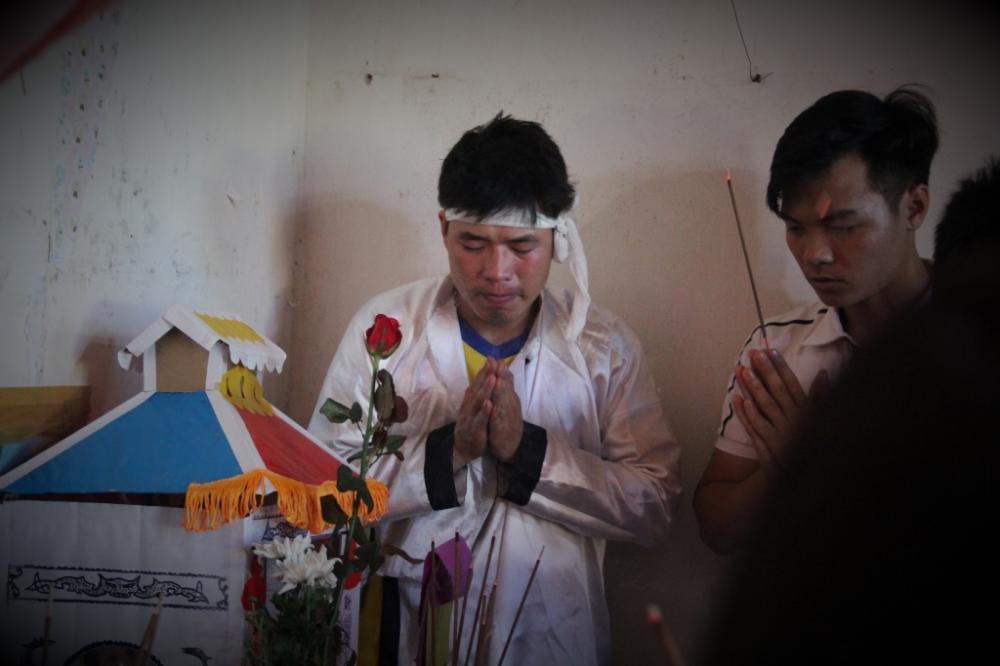 Anh Hoàng bên bàn thờ hai người con. (Ảnh: Hoài Nam)
