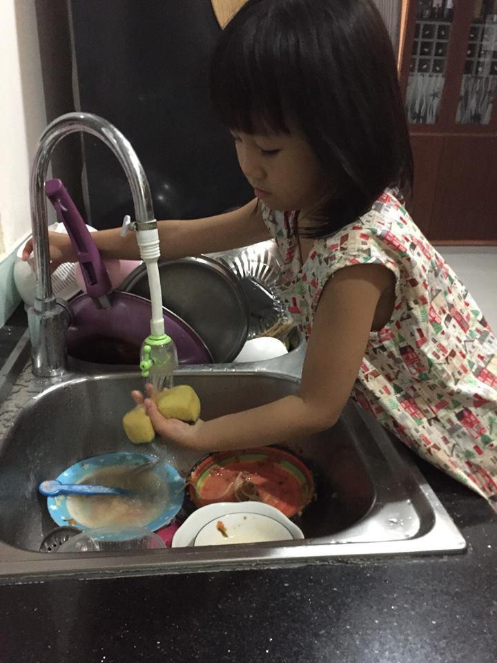 Bé Ngọc 5 tuổi giúp mẹ rửa bát.