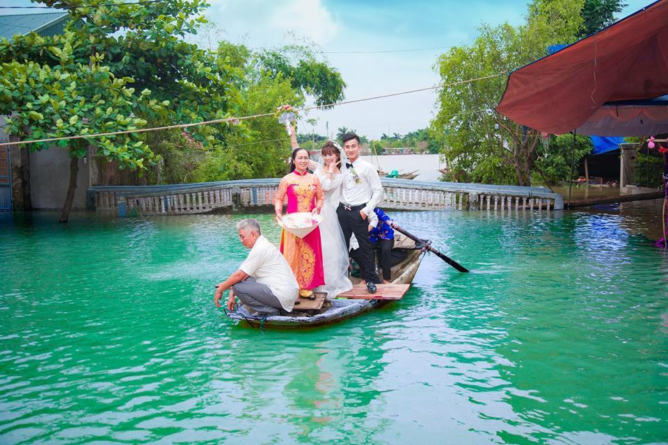 Cô dâu chú rể cười tươi trên thuyền.