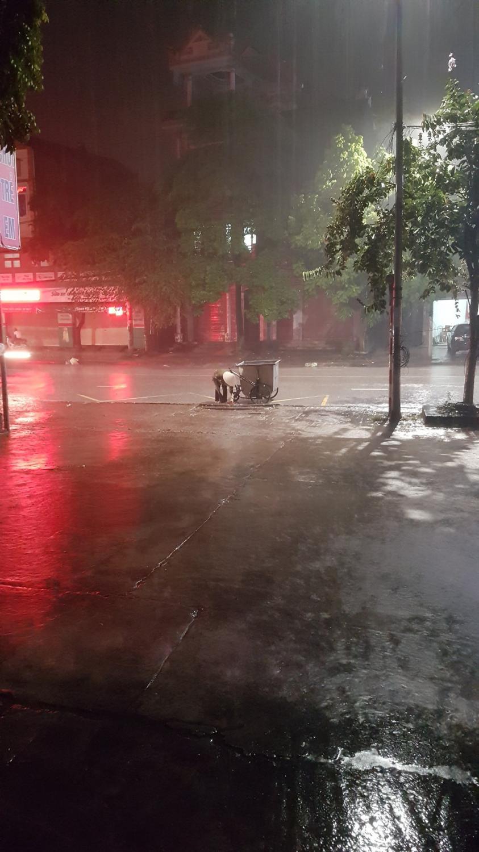 Hình ảnh cô lao công vẫn đang cặm cụi nhặt rác dưới mưa tránh bị trận mưa cuốn xuống gây tắc cống