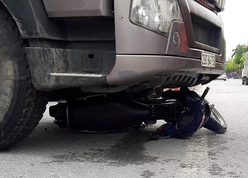 Chiếc xe máy bị cuốn vào gầm xe tải