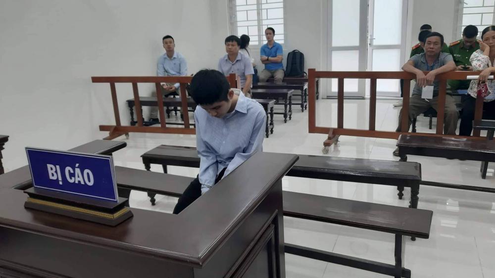 Bị cáo ủ rũ trước bục gỗ trong phòng xử án