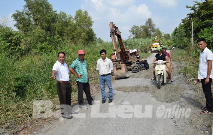 Chủ tịch UBND huyện Vĩnh Lợi - Từ Minh Phúc (bìa trái) kiểm tra tiến độ sửa chữa tuyến đường Châu Hưng - Hưng Thành. Ảnh: M.Đ