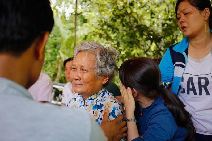 Bà Hạnh (mẹ anh Phong) trong vòng tay họ hàng tại đám tang con