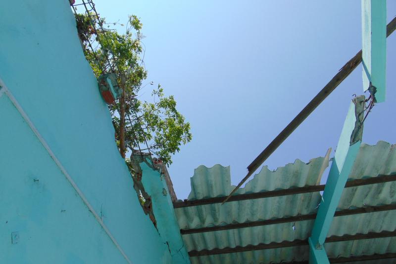 Căn nhà trước của bà Cúc bị hư hỏng nặng do cần cẩu của chiếc xáng cạp rơi trúng - Ảnh: Gia Minh