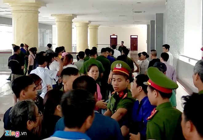 Cảnh sát vất vả vãn hồi trật tự khi đưa bị cáo rời tòa. Ảnh: Hoàng Lam.