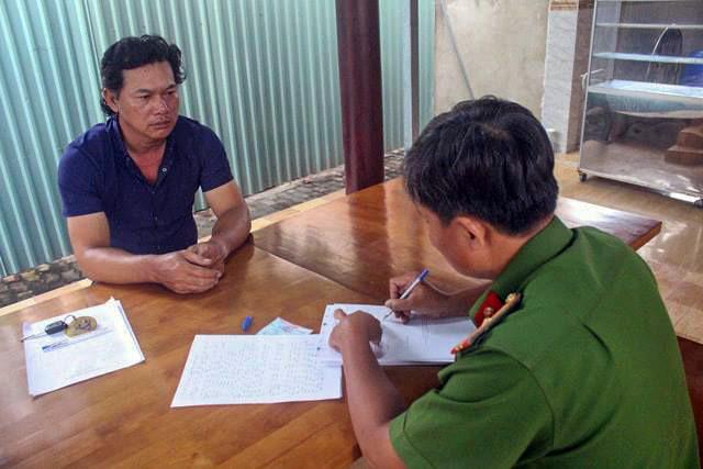 Nghi can Nguyễn Văn Xuân (á đen) đến công an đầu thú. Ảnh: V.D.