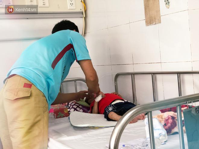 Anh Ch. lau mặt cho con trai sau khi bé khóc ré lên từng hồi vì đau.
