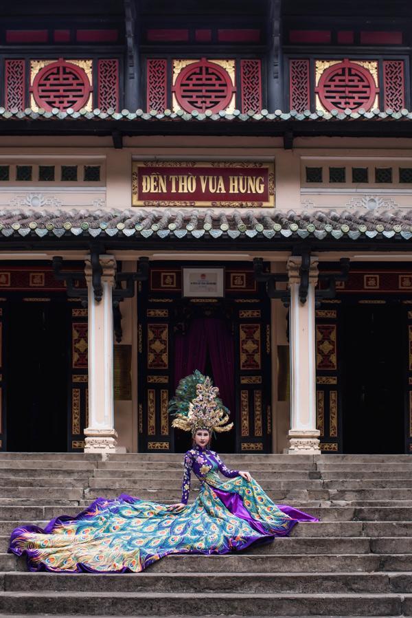 Phần mấn đội đầu đính kết rất cầu kỳ, tà áo dài phía sau cách điệu xòe rộng, họa tiết rực rỡ, giúp Chi Nguyễn hóa thân một nàng chim công xinh đẹp.