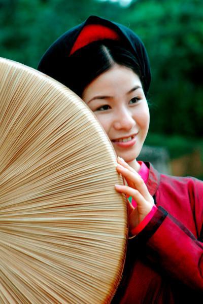 Người phụ nữ e ấp bên vành nón quai thao.