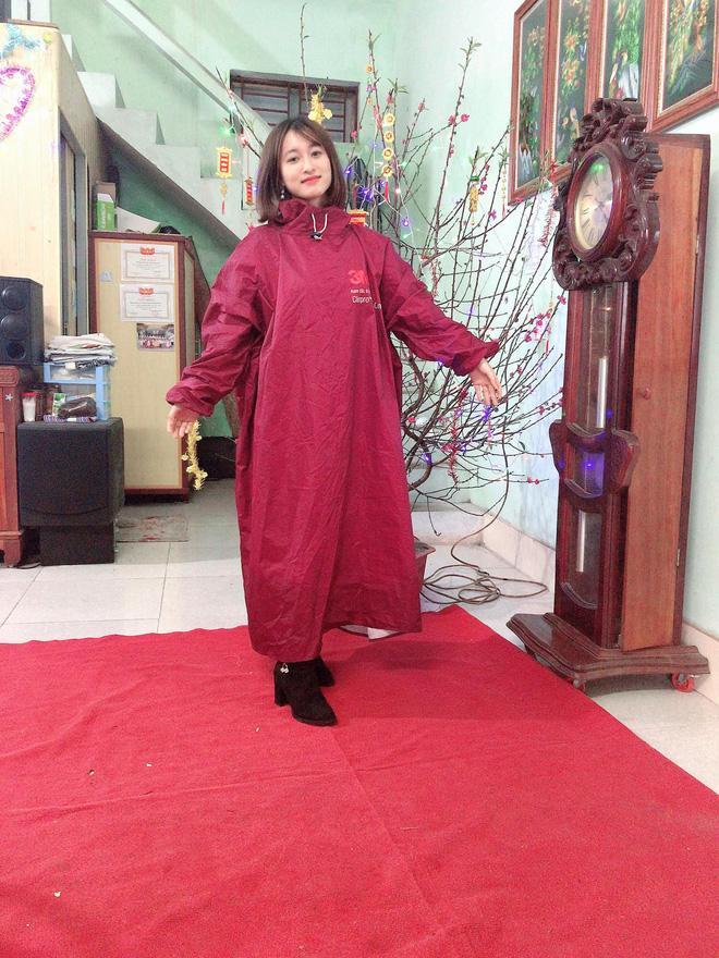 Dù diện đồ rất đẹp nhưng cô gái không quên khoác thêm chiếc áo mưa đỏ bắt trend trong ngày mồng 1 Tết